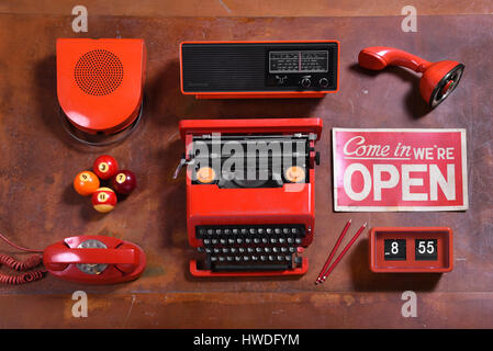 High Angle Still Life of Collection of Red Objects on Wood Desk - Speaker, Radio, Typewriter, Open Sign, Clock, - Stock Photo