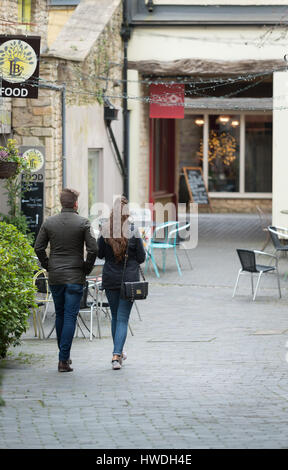 A young man and woman walk through Swan Yard looking at the shops, Cirencester in the Cotswolds, Gloucester, England, - Stock Photo