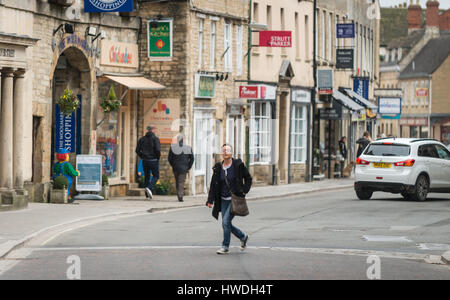 Woman walks across Market Place, Cirencester in the Cotswolds, Gloucester, England, UK - Stock Photo