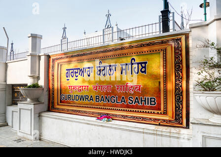 Colourful golden name sign at the entrance of Gurudwara Bangla Sahib, a Sikh temple in New Delhi, capital city of - Stock Photo