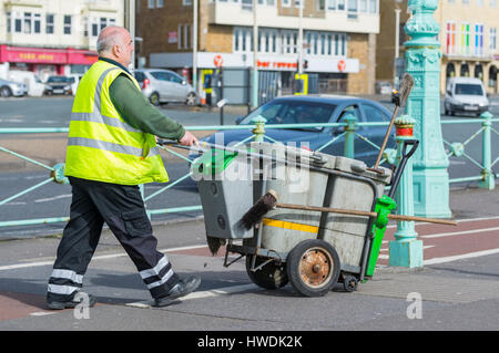Male council street cleaner pushing a little bin in Brighton, East Sussex, England, UK. - Stock Photo