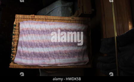 A lovely soft hand knitted baby blanket in colours of pastel shades of pinks, lilac, through to whites. The blanket - Stock Photo