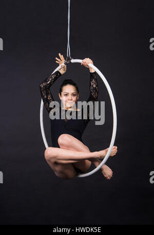 Aerial acrobat in the ring. A young girl performs the acrobatic elements in the air ring. Studio shooting performances - Stock Photo