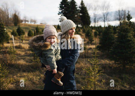 Mother and baby girl in Christmas tree farm, Cobourg, Ontario, Canada - Stock Photo