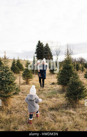 Mother and baby girls in Christmas tree farm, Cobourg, Ontario, Canada - Stock Photo