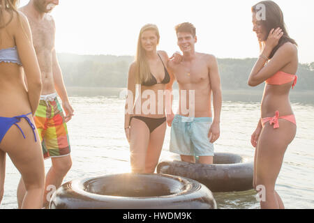 Friends having fun with inflatable ring in river - Stock Photo