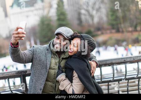 Couple taking smartphone selfie on city balcony - Stock Photo