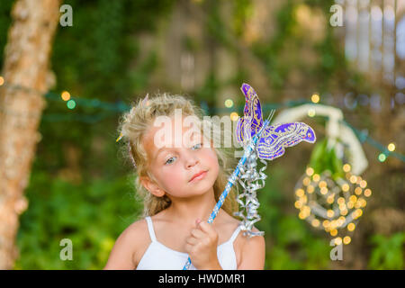 Portrait of young girl holding butterfly wand - Stock Photo