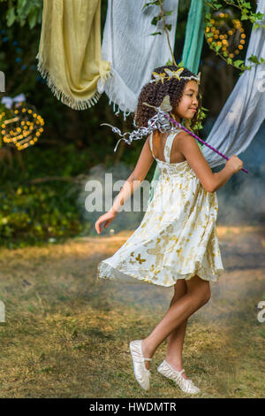 Young girl dressed as fairy, holding wand, playing outdoors