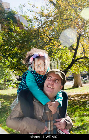Father giving smiling daughter piggy back - Stock Photo