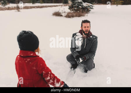 Girl throwing snowball at her father - Stock Photo
