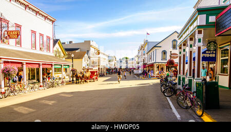 Mackinac Island, Michigan, August 8, 2016: Vacationers take on Market Street on Mackinac Island that is lined with - Stock Photo