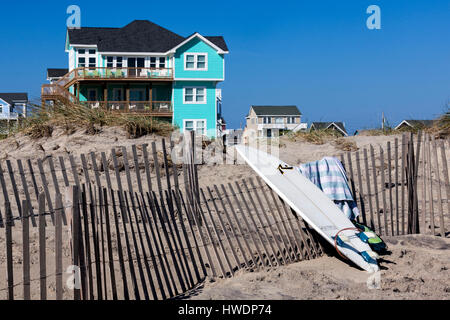NC00746-00...NORTH CAROLINA - Surfboard, sand fence and beach houses at Rodanthe on the Outer Banks, Cape Hatteras - Stock Photo