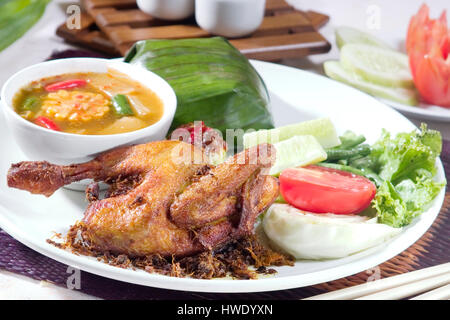 Ayam goreng Fried chicken Food Indonesia, serve with tamarind dish, sayur asam and rice - Stock Photo