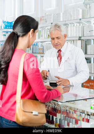Chemist Swiping Card While Customer Standing In Pharmacy - Stock Photo