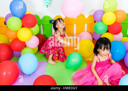 Asian Little Chinese Girls Playing with Colorful Balloons in Indoor Playground - Stock Photo