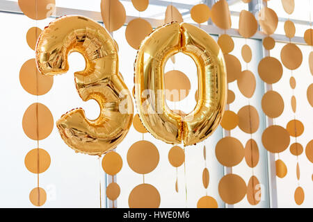 Golden balloons with ribbons - Number 30. Party decoration, anniversary sign for happy holiday, celebration, birthday, - Stock Photo