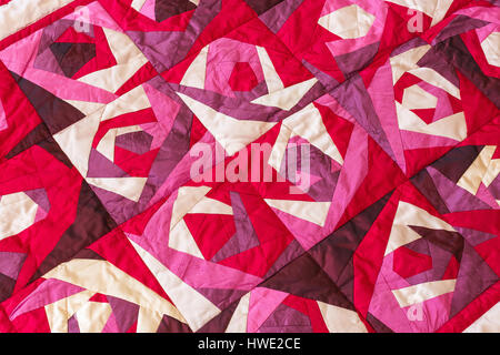 Part of color patchwork quilt with purple flowers pattern as background. Pink Scrappy blanket. Hobby Concept. - Stock Photo