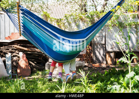 Children's feet in blue hammock on a background of nature greenery. - Stock Photo