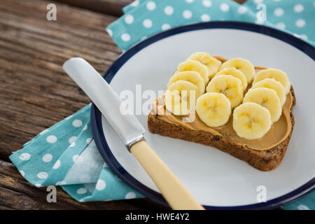 Sliced bananas spread on brown bread in plate on wooden table - Stock Photo