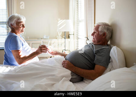 Senior woman giving medicine to senior man in the bedroom at home - Stock Photo