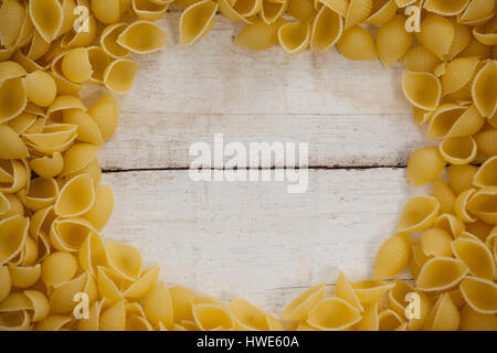 Conchiglie pasta isolated on wooden table - Stock Photo