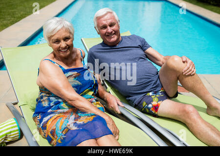 Portrait of senior couple relaxing on lounge chair at poolside - Stock Photo