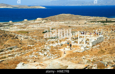 Tourists explore the mythological island of Delos, off the coast of Mykonos in the Greek Islands. - Stock Photo