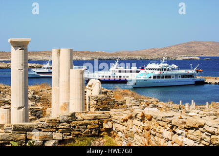 Visiting tour boats at the small port on the mythological island of Delos, off the coast of Mykonos in the Greek - Stock Photo