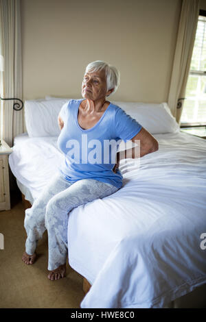 Senior woman suffering from backache in the bedroom at home - Stock Photo