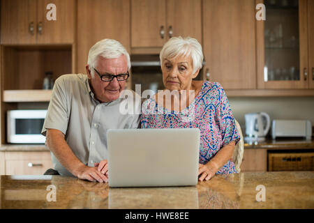 Senior couple using laptop in the kitchen at home - Stock Photo