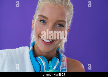 Portrait of beautiful woman smiling against violet background - Stock Photo