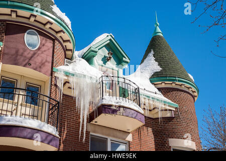 Big icicles and snow hanging from the roof in Montreal - Stock Photo