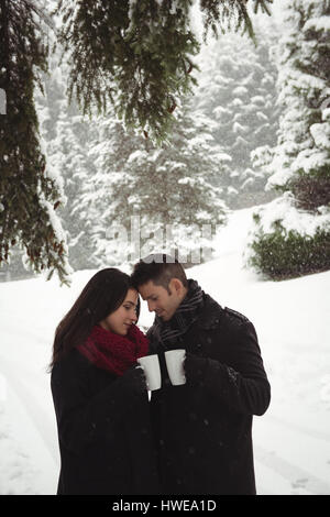 Romantic couple having cup of coffee in winter forest - Stock Photo