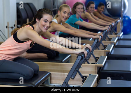 Portrait of smiling women practicing stretching exercise on reformer in gym - Stock Photo