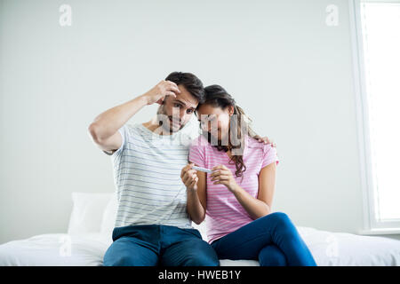 Couple finding out results of a pregnancy test in bedroom at home - Stock Photo
