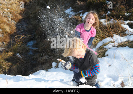 Children having a snowball fight with full impact - Stock Photo
