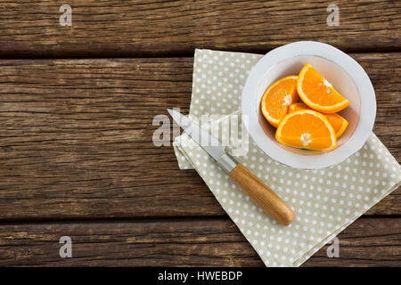 Overhead of oranges slices in bowl on wooden table - Stock Photo