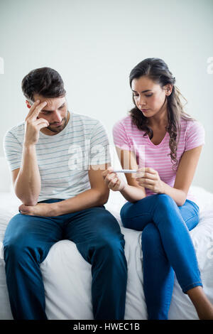 Worried couple finding out results of a pregnancy test in bedroom at home - Stock Photo
