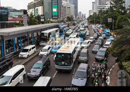 JAKARTA, INDONESIA - JANUARY 27, 2017: Cars, buses and motorcycles try to move in a traffic jam in the business - Stock Photo