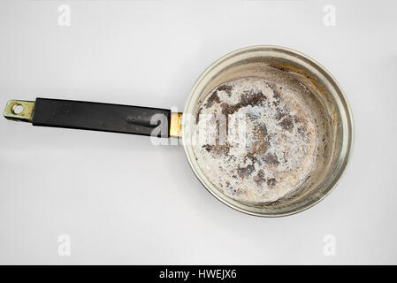 Pan with burnt food on white background - Stock Photo