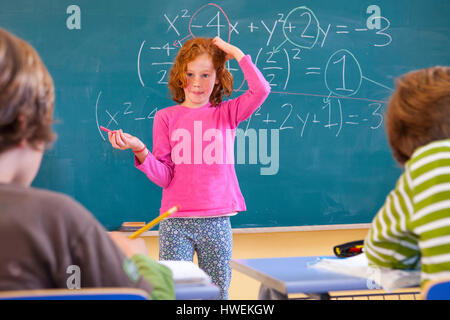 Primary schoolgirl scratching her head at equation on classroom blackboard - Stock Photo