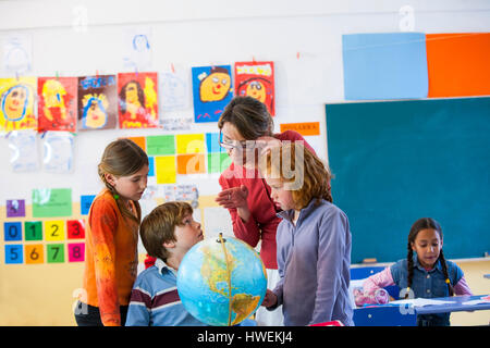 Primary school teacher and schoolchildren looking at globe in classroom - Stock Photo