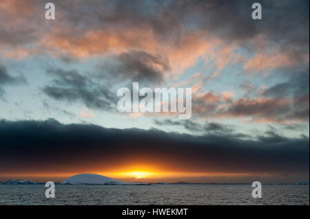 Sunset over icebergs in Lemaire channel, Antarctica - Stock Photo