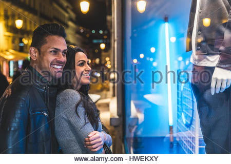 Couple in city at night, looking in shop window, Lisbon, Portugal