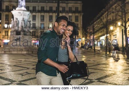 Couple walking through city, at night, Lisbon, Portugal - Stock Photo