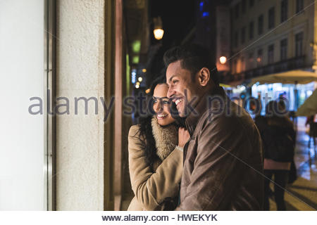 Couple looking in shop window, at night, Lisbon, Portugal - Stock Photo