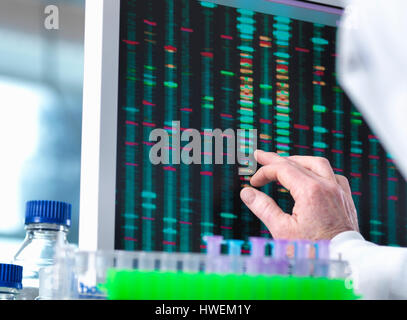 DNA Research, Scientist viewing DNA test results on a computer screen in the laboratory with a tray of samples in the foreground
