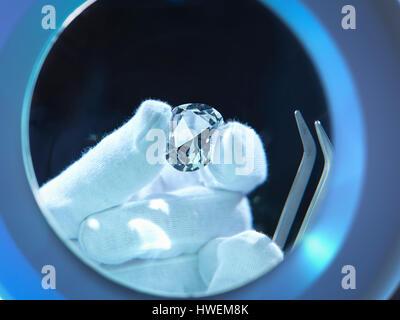 Jeweller inspecting replica diamonds with gloved hand - Stock Photo