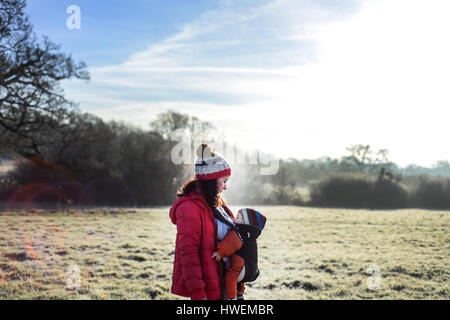 Woman in rural setting, carrying young baby in sling - Stock Photo